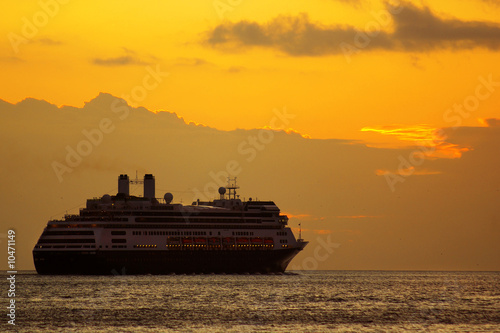 Large cruise ship at sunrise in a journey into the horizon