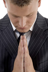 praying young businessman against white background