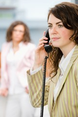 Businesswomen at office, receptionist calling on phone.