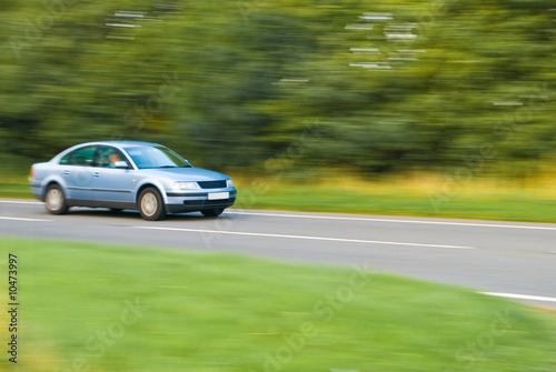 Car travelling down country lane, panned motion blur