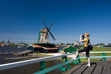 Happy tourist with photo camera and Dutch mill on the waterside
