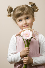 Shy litlle girl with pink gerber daisy