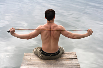 A man warms-up with skipping-rope sitting on wooden bridge