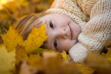 Head of girlie lying on golden leaves peacefully