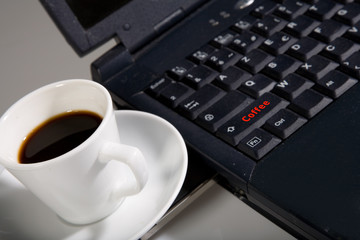 cup with black coffee with laptop