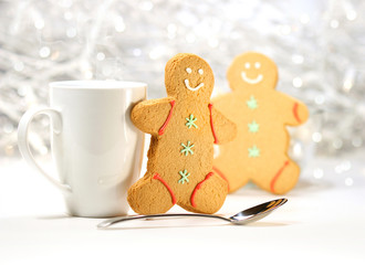 Hot holiday drink with gingerbread cookies on festive background