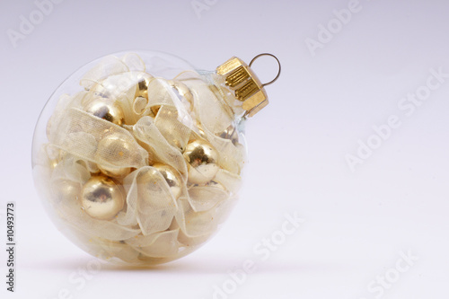 gold christmas-tree ball in the light lilac background