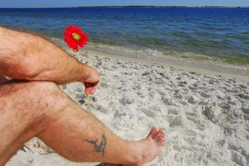 Man holding flower on beach