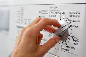 a hand is adjusting the washing program (german)
