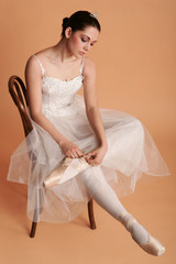 Ballerina sit on the chair and tie up her shoes