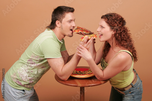 Young man and young woman feed pizza to each other - 10506523