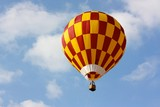 A colored hot air balloon flying in a sunny sky