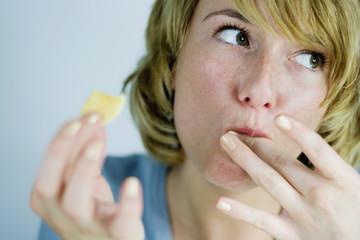 Junge Frau isst einen Keks und leckt sich die Finger, lecker