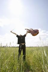 Junger Mann, der im Feld steht, mit Cello
