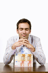 Junger Mann mit einem Haus aus Geldscheinen, Euro