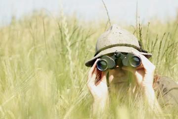 Junge Frau mit Fernglas im Weizenfeld