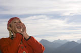 Young woman in mountains shouting, low angle view, portrait
