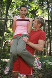 Young couple exercising on horizontal bar, smiling