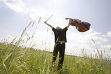 Young cellist in field, arms up