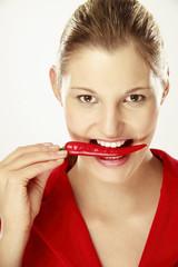 Junge Frau mit Chilischoten zwischen den Zähnen