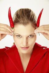 Junge Frau mit Chili auf Kopf, Hörner simulieren