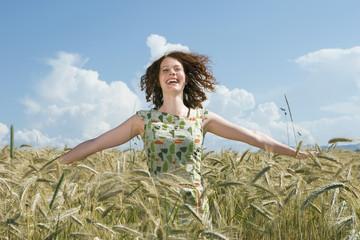 Junge Frau im Kornfeld, die Arme ausgetreckt