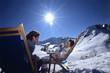 Junges Paar sitzt auf Liegestühlen in den Alpen, lächelnd