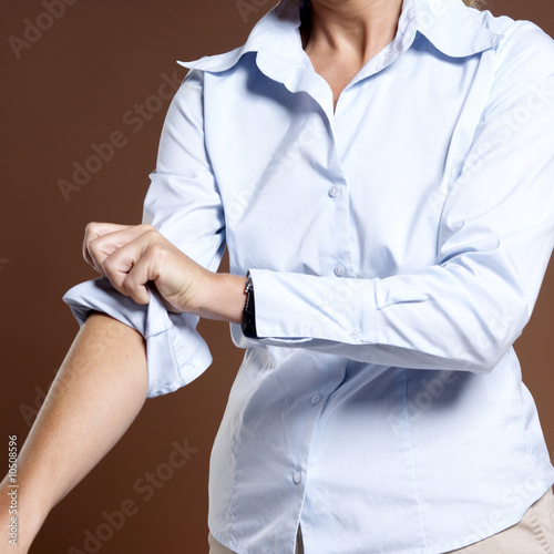 Businesswoman rolling up shirt sleeves, close-up