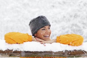 Junge Frau im Schnee stützte sich auf Holzgeländer