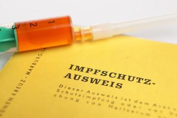 Spritze und Impfpass, close-up