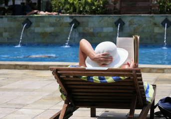 The woman reading in a chair about a swimming pool