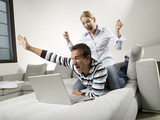 Couple on sofa, using laptop