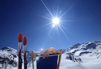 Person sitzt im Liegestuhl in den Alpen, Winter