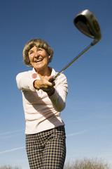 Deutschland, Bayern, Ammersee, Seniorin Frau Golfschläger schwingen, lächeln,