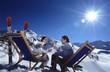 Paar sitzt auf Liegestühlen im Schnee, prosten sich zu