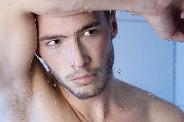 Junger Mann unter der Dusche hinter Glasscheibe