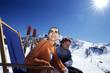 Paar entspannt auf Liegestühlen in den Alpen, lächelnd