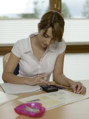 Teenager, Mädchen sitzt am Schreibtisch, mit Taschenrechner