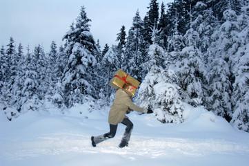 Junger Mann mit Weihnachtsgeschenk im Schnee, Seitenansicht