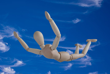 A wooden mannequin in a skydiving freefall in a blue cloudy sky