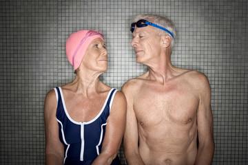 Älteres Paar im Umkleideraum, trägt Badekappe und Brille