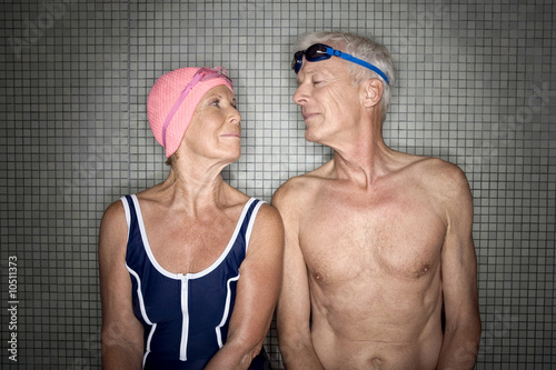 Senior couple in changing room, wearing swim cap and goggles