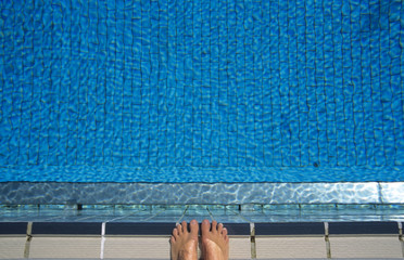 Füße am Rand des Schwimmbades