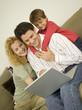Junge Familie im Wohnzimmer, der Vater mit Laptop