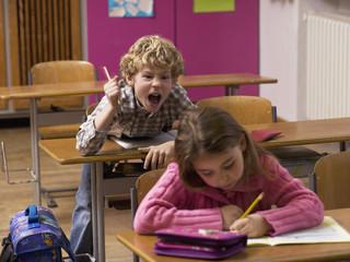 Junge schreien hinter Mädchen in Klassenzimmer