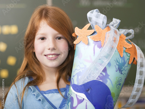 Girl (6-7) holding school cone, smiling, portrait, close-up