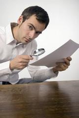 Junger Mann studiert ein Dokument mit einer Lupe