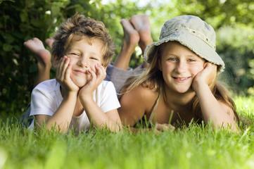 Junge und Mädchen liegen im Gras