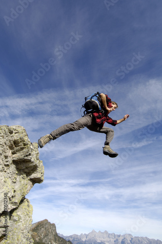 Man jumping from mountain peak, low angle view