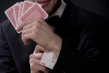 Mann hält Spielkarten, As im Ärmel